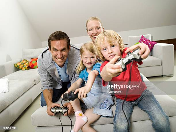 Parents with children (6-9) playing video game, smiling