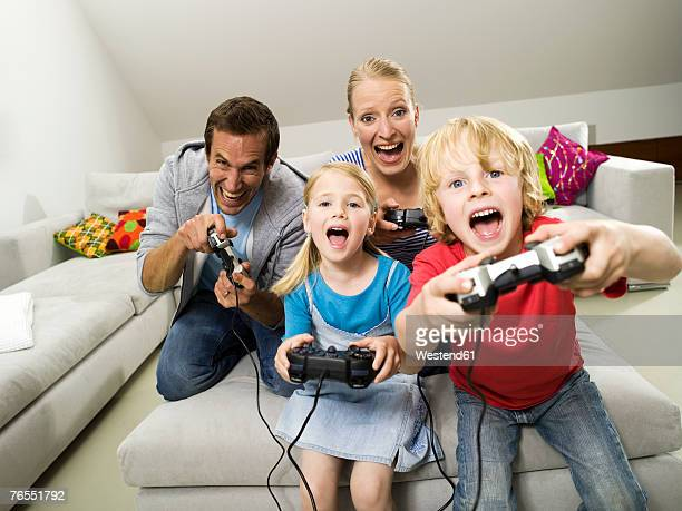 Parents with children (6-9) playing video game, laughing