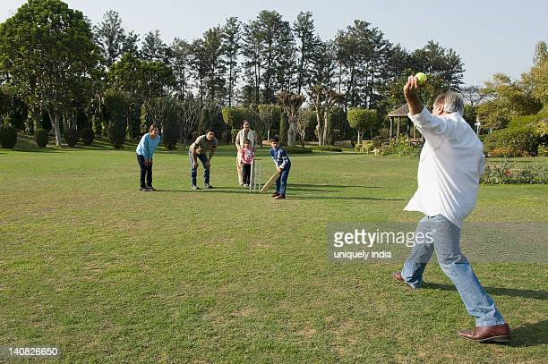 Family playing cricket in lawn