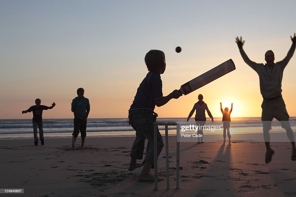 family playing cricket on beach at sunset : Stock Photo