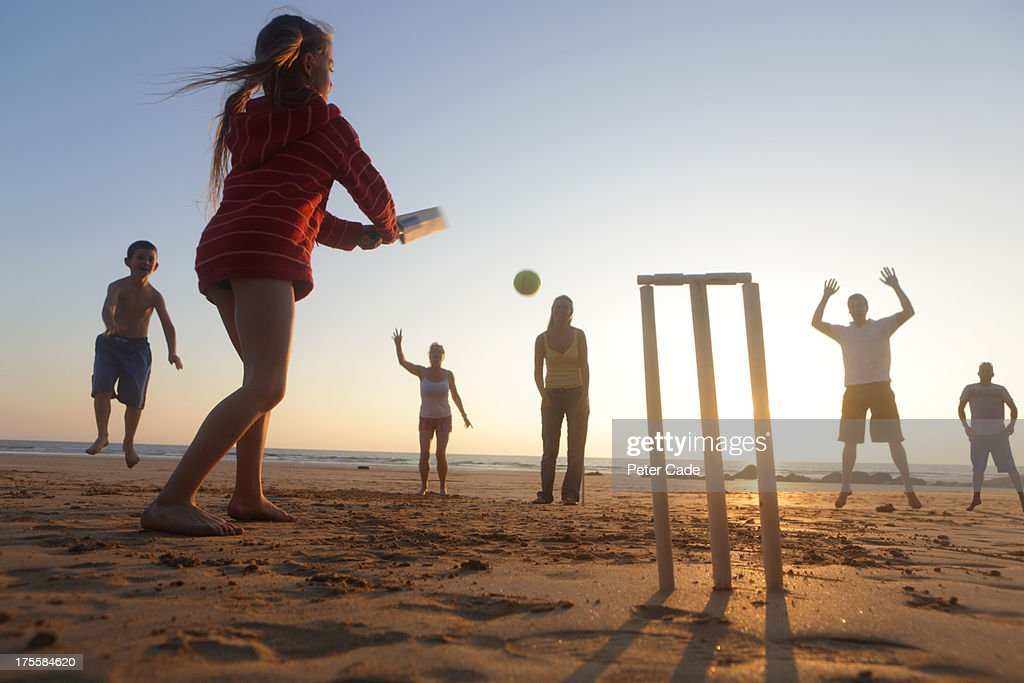 Family playing cricket on beach : Stock Photo