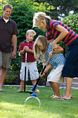 family playing croquet in the backyard