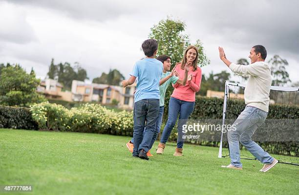 Family playing football and celebrating a goal