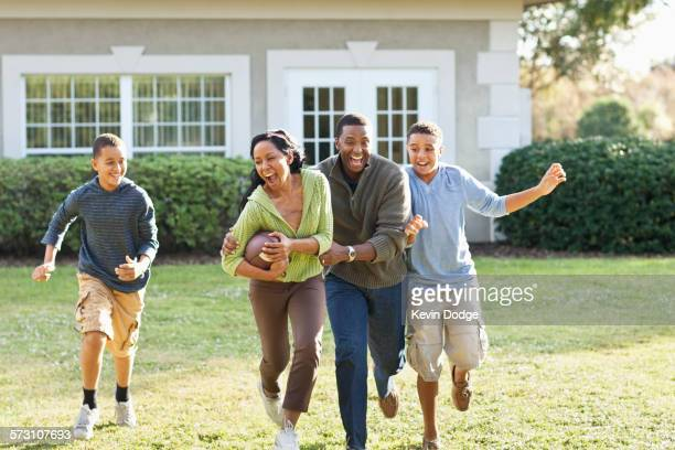 Family playing football in backyard