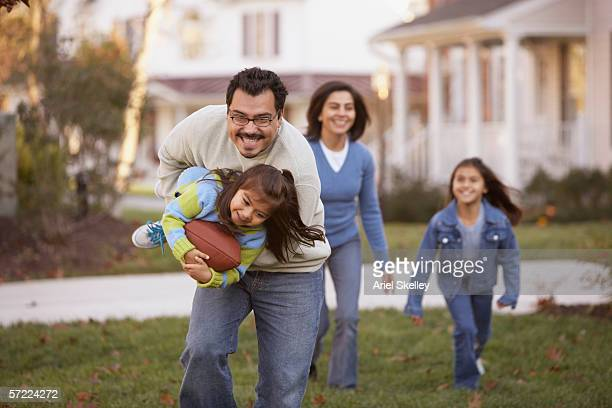 Family playing football in front yard