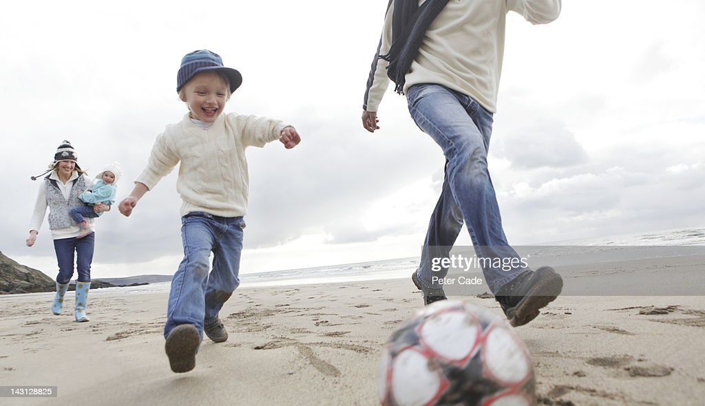 family playing football on beach in winter : Stock Photo