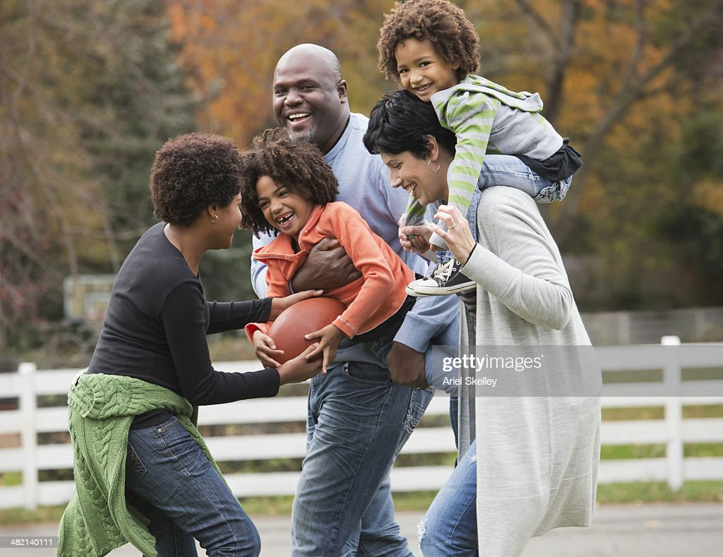 Family playing football together outdoors