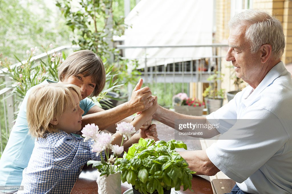 Family playing funny games on balcony table : Stock Photo