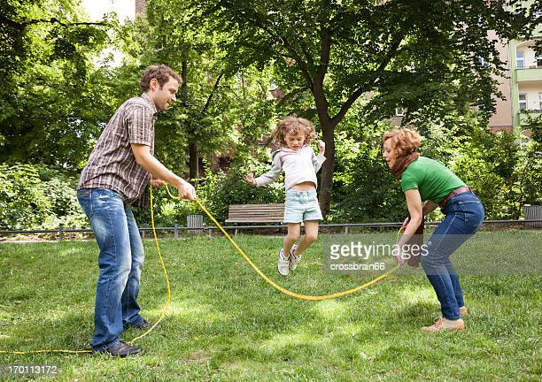family playing games outdoors - young girl skipping rope
