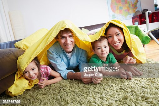 Father And Children Playing In Blanket Fort Living Room Stock