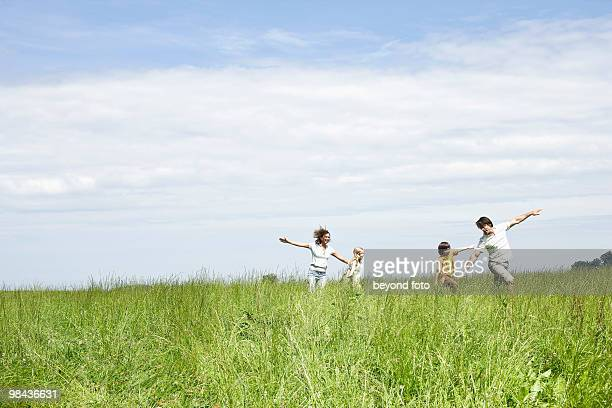 family playing in meadow