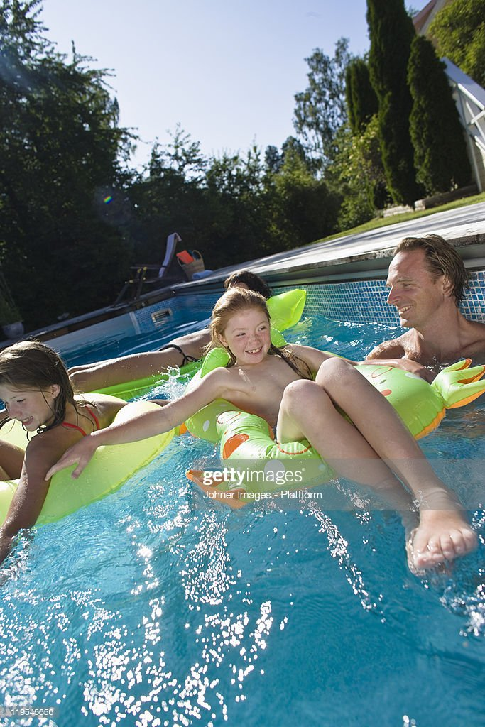 Family playing in swimming pool stock photo getty images for Pool show discovery