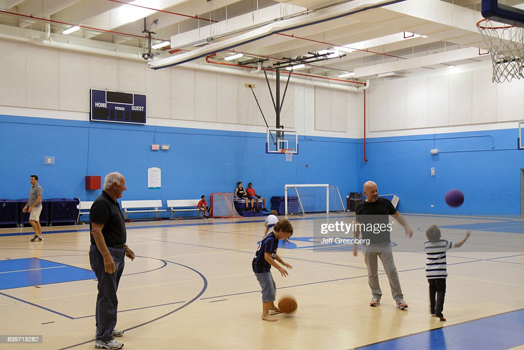 a family playing in the indoor basketball court at scott rakow community center