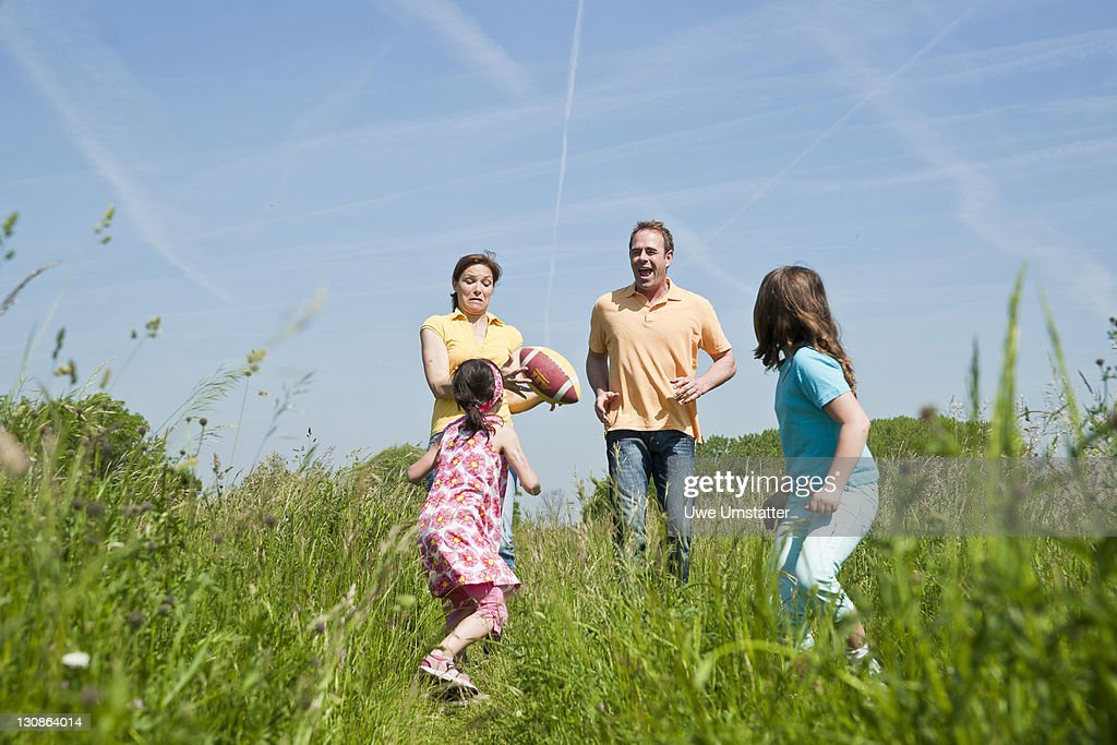Family playing joyfully with a ball in a flower meadow : Stock Photo