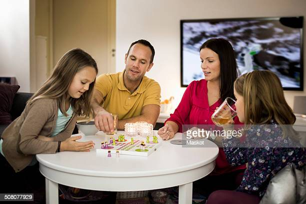 Family playing ludo in living room