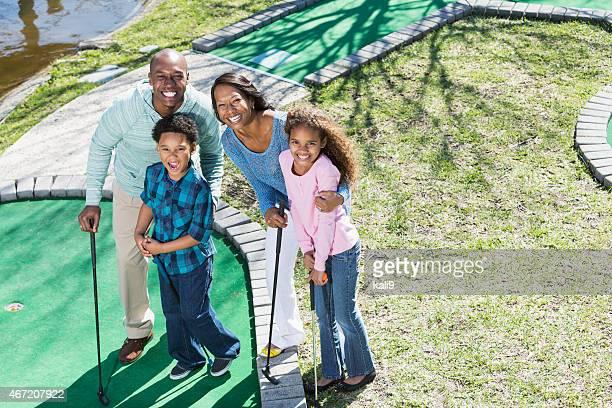 Familie spielt Minigolf