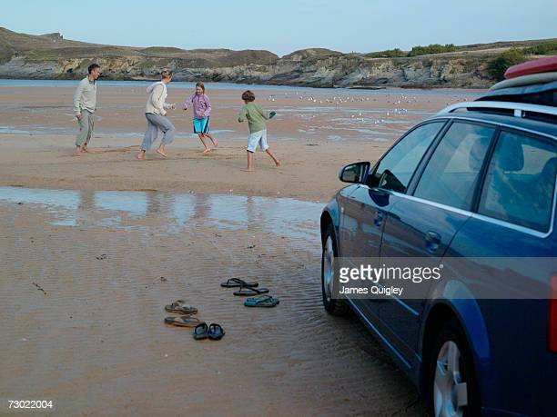 'Family playing on beach, with car'
