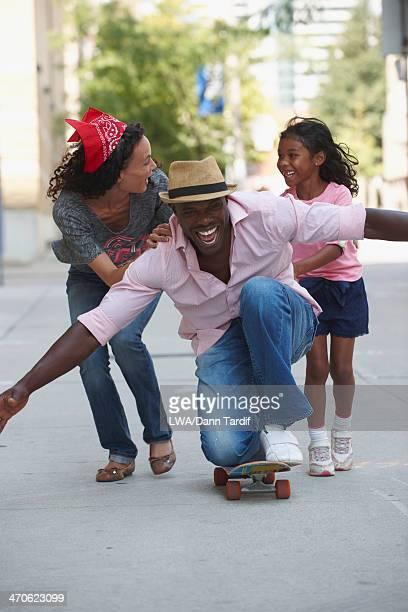 Family playing on skateboard on urban sidewalk