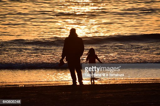 A family playing on the sunset beach : ストックフォト