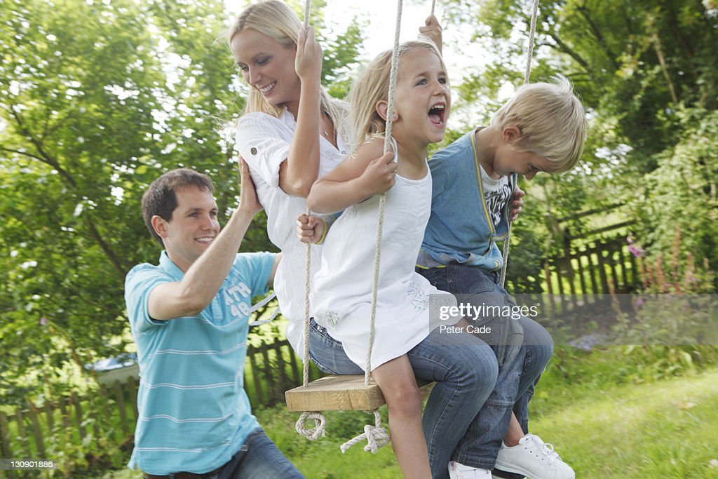 family playing on tree swing : Stock Photo