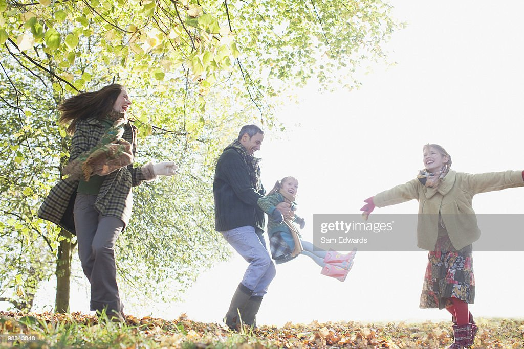 Family playing outdoors in autumn