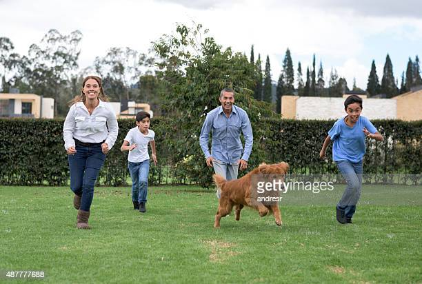 Family playing outdoors with their dog