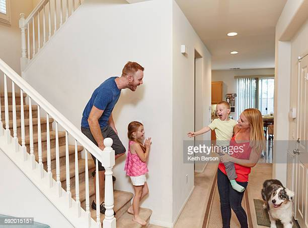 Family playing peek-a-boo on staircase at home