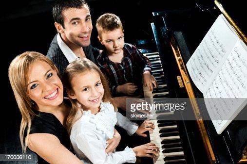 Family playing piano and looking at camera