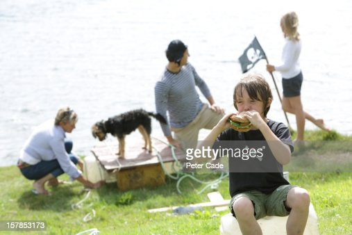 Family playing pirates by water with picnic : Stock Photo
