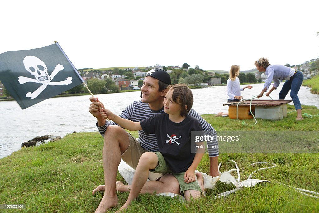 Family playing pirates by water with raft and flag : Stock Photo
