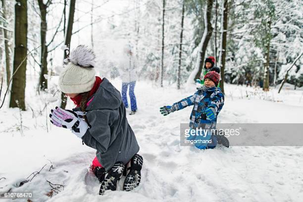 Family playing showball fight in winter forest