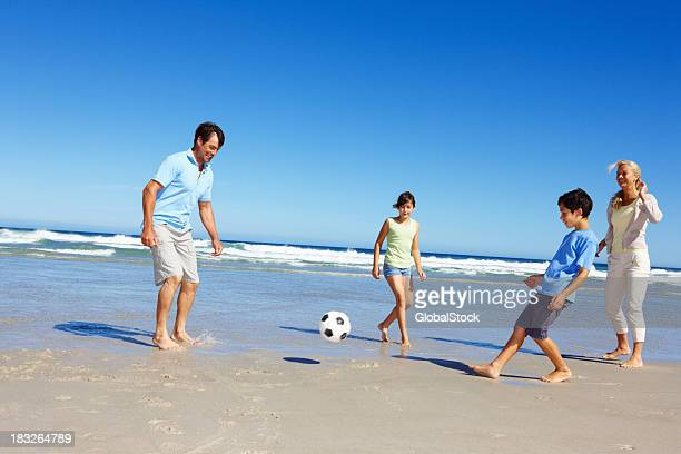 Family playing soccer along the beach