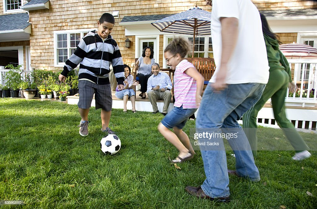 Family playing soccer in suburban backyard : Stock Photo