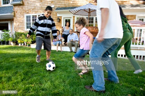 Family playing soccer in suburban backyard