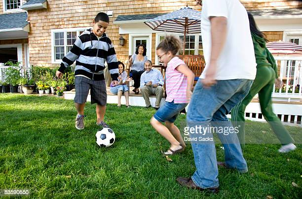 Family playing soccer in suburban backyard
