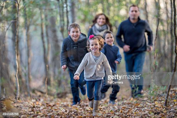 Family Playing Tag in the Woods