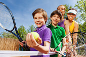 Close-up portrait of smiling active family, holding tennis rackets and ball on the court in sunny day
