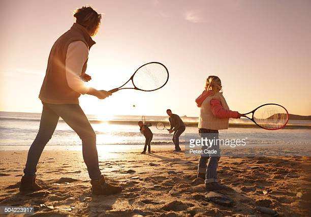 Family playing tennis on beach at sunset