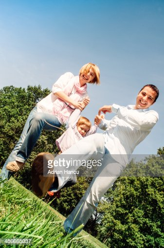 Family playing (swinging) together in green park : Stock Photo