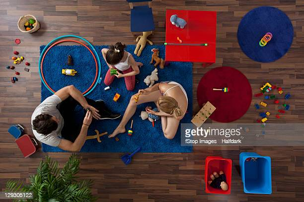 A family playing together in their living room, overhead view