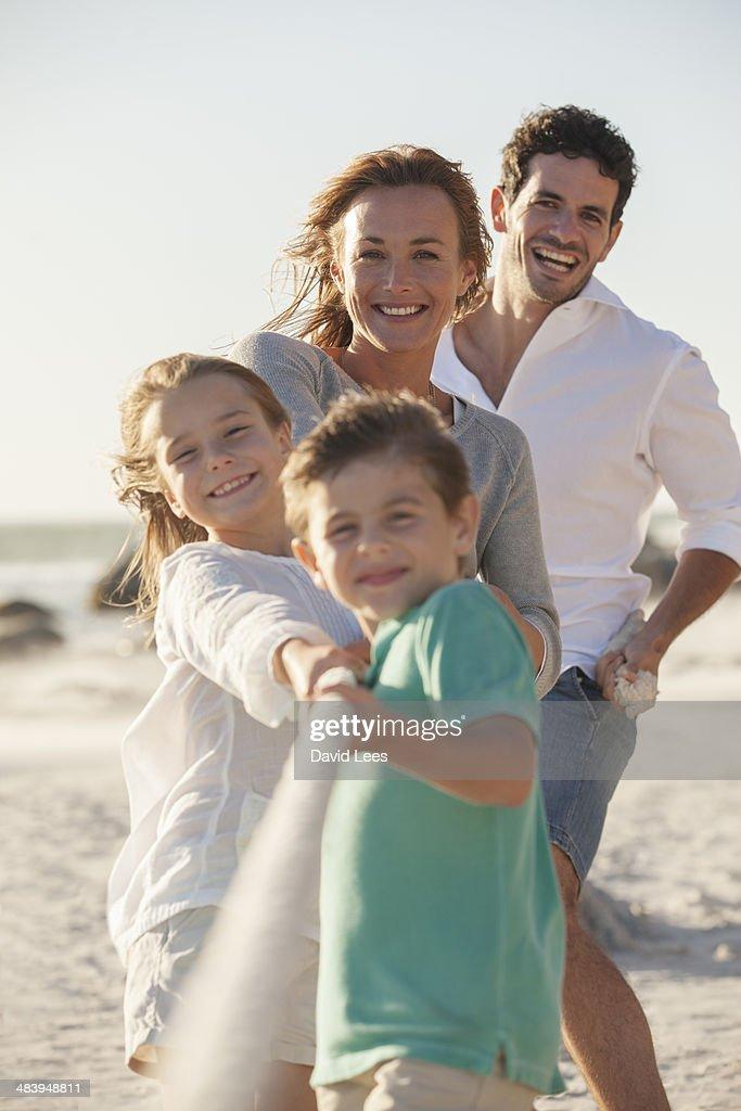 Family playing tug of war on beach : Stock Photo