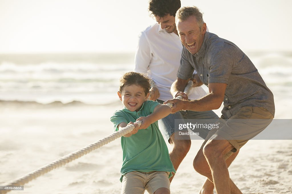 Family playing tug of war on beach