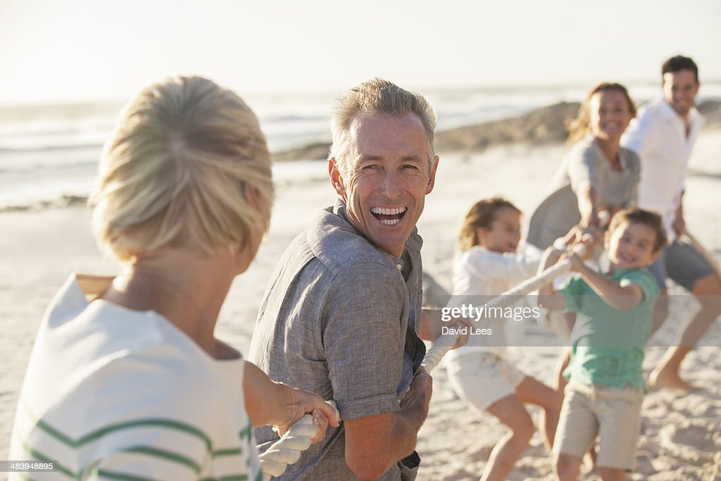 Family playing tug of war on beach : Stock Photo