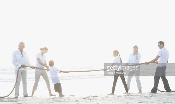Family playing tug-of-war at beach