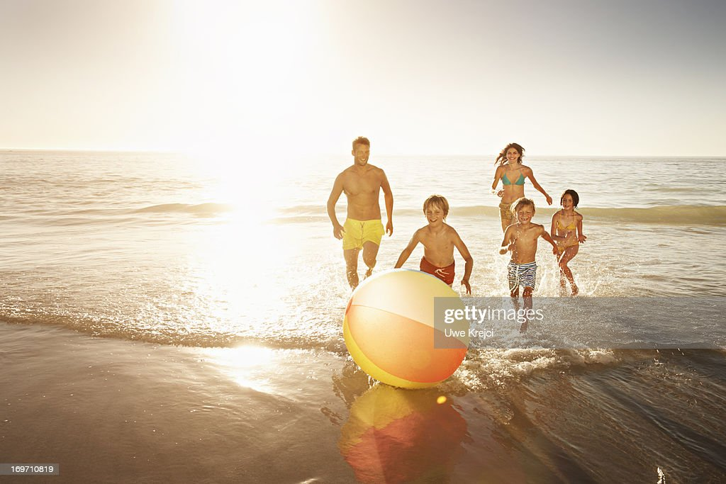 Family playing with a beach ball by the sea