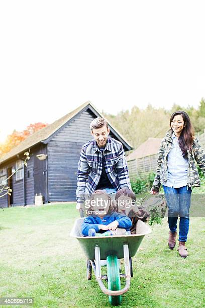 Family playing with a wheelbarrow in their garden.