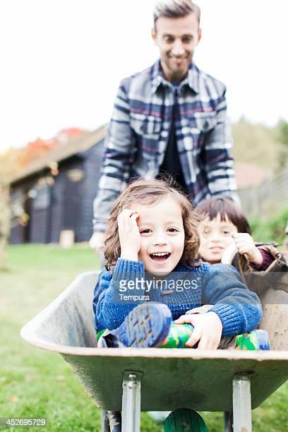 Family playing with a wheelbarrow in their garden.