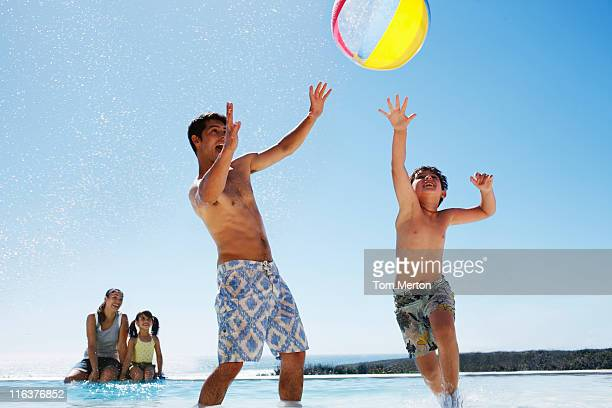 Family playing with ball in swimming pool