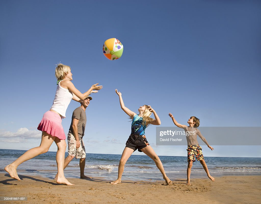 Family playing with beach ball on beach, low angle view : Stock Photo