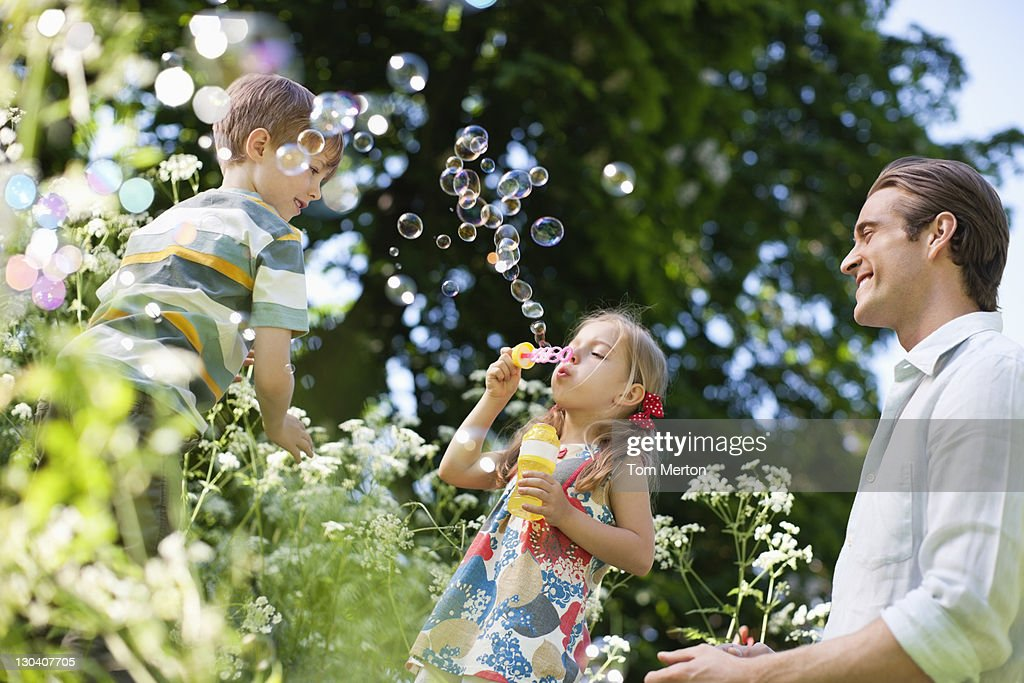 Family playing with bubbles outdoors : Stock Photo